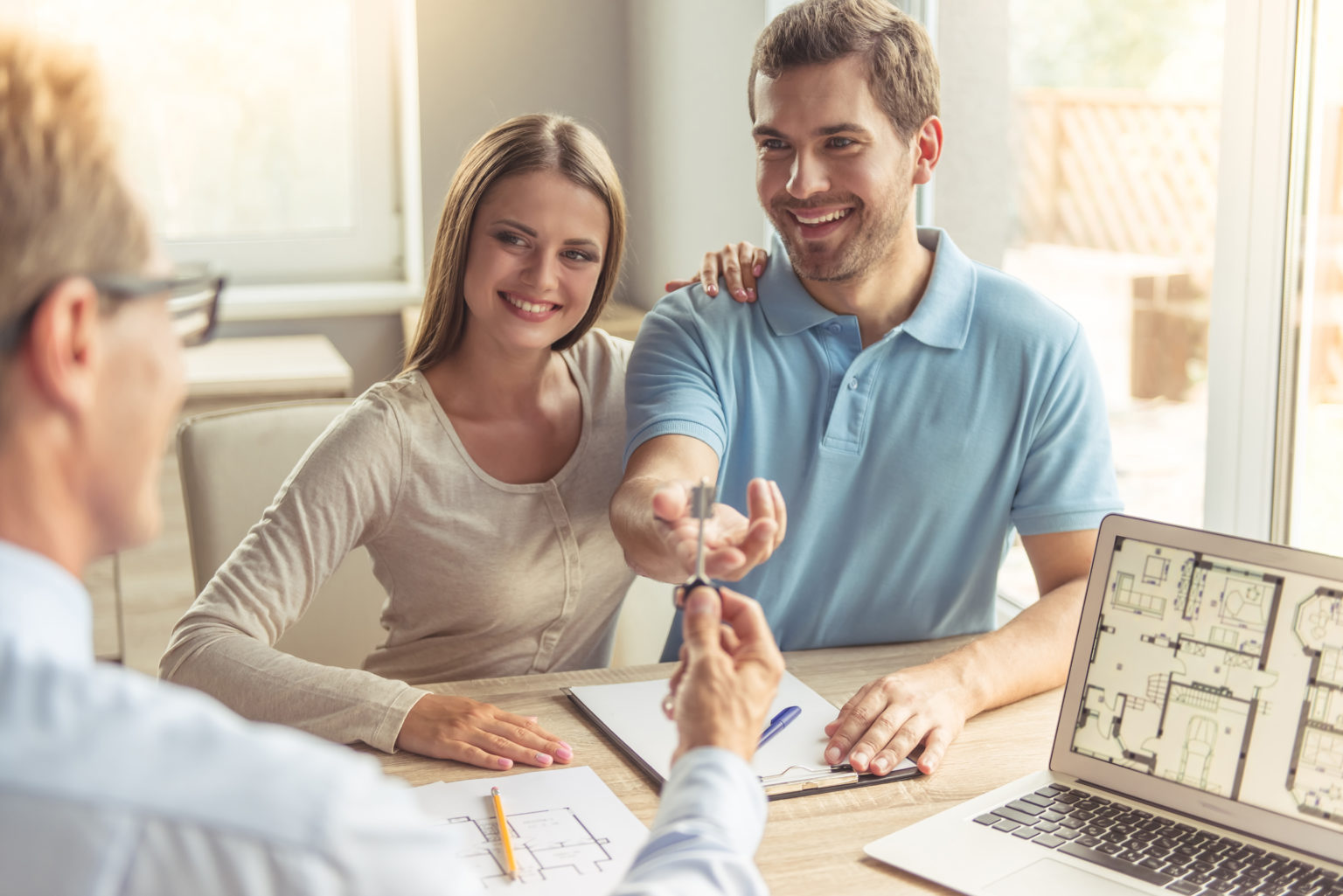 Handsome realtor in classic shirt is giving key of the new apartment to happy young couple while they are sitting in the office